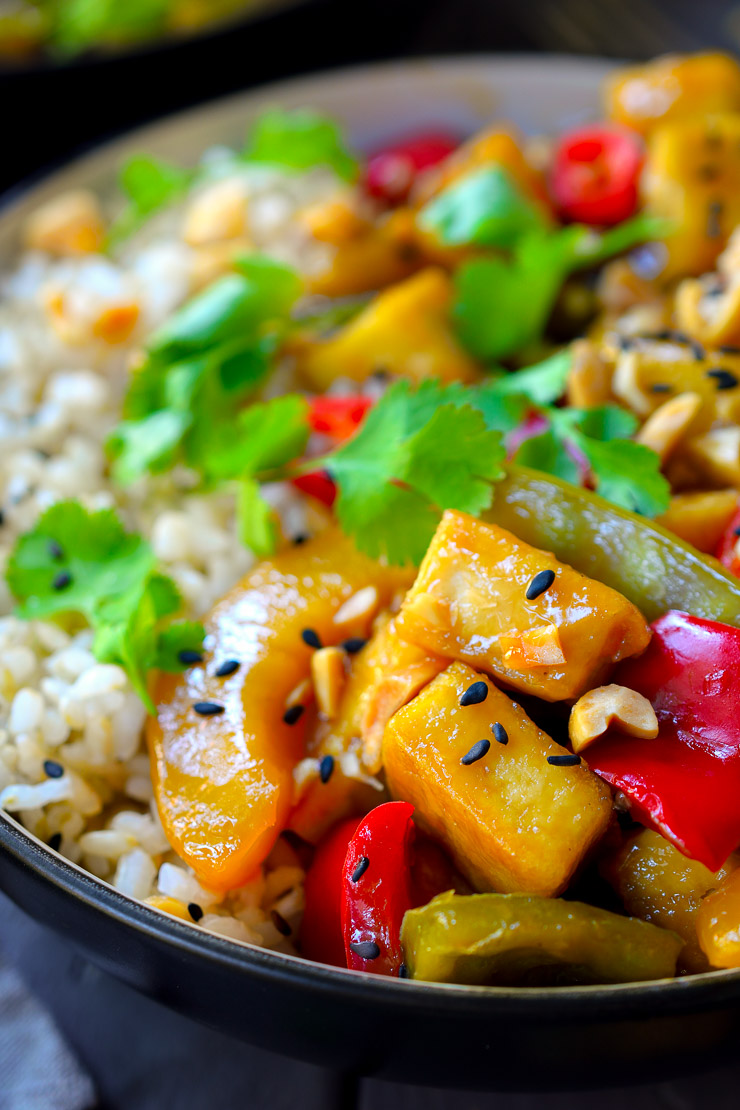 This sweet and sour tofu is better than take out with crisp peppers, peaches, pineapple and snow peas. A quick vegan meal.