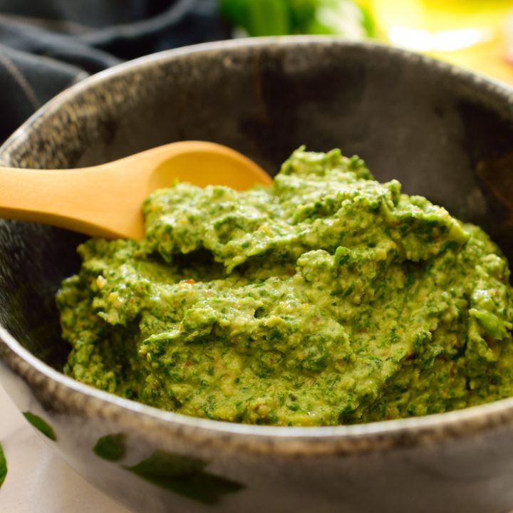 Vegan pesto in a black bowl with a wooden spoon.