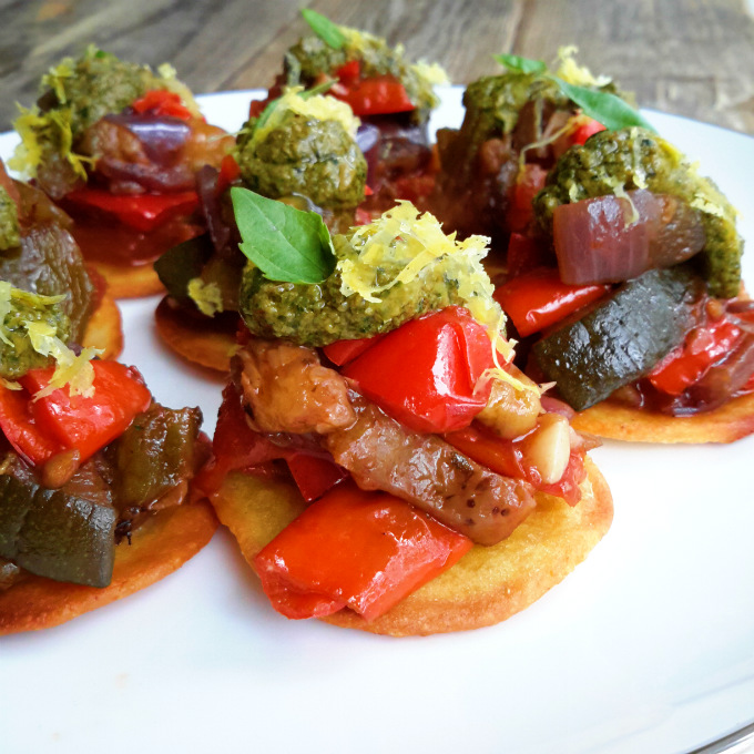 Fresh, sweet ratatouille served on mini socca bites and topped with vegan pesto. Delicious finger food for your next party!