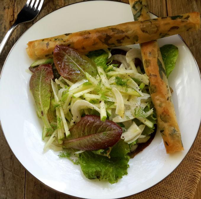 Una deliciosa ensalada de manzana y hinojo servida con cigarros de filo rellenos de tapenade y hierbas frescas para un entrante elegante y vegetariano.