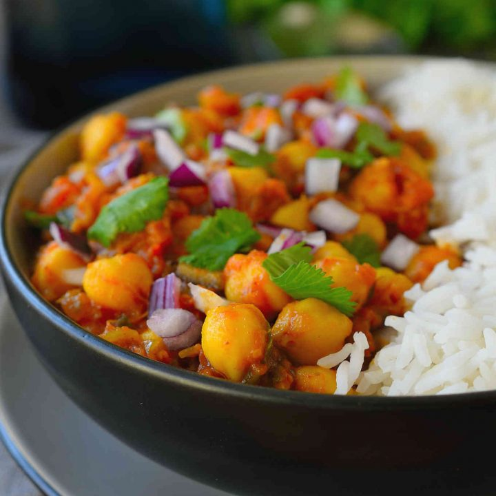 Vegan chickpea curry is an easy and flavourful tomato-based curry great for a weeknight dinner. Adjust the spice level to your preference with this recipe and feel free to add in other greens and veggies like kale, spinach or broccoli for a healthy and satisfying meal!