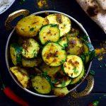 Este plato sencillo de patatas y calabacín con especias indias esta lleno de sabor! Dos ingredientes principales y un manojo de especias es todo lo que necesitas para este plato vegano o vegetariano. Se puede servir para acompañar otro plato o con arroz y naan o chapati.