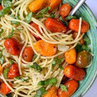 """Esta receta para pasta vegana con tomates asados, ajo y albahaca es tan fácil que se puede poner en la categoría de """"cocina para torpes"""". Adelante, intenta estropearlo, te reto. Necesitarás en total siete ingredientes y tan sólo veinticinco minutos para poner este plato sencillo y colorido en la mesa."""