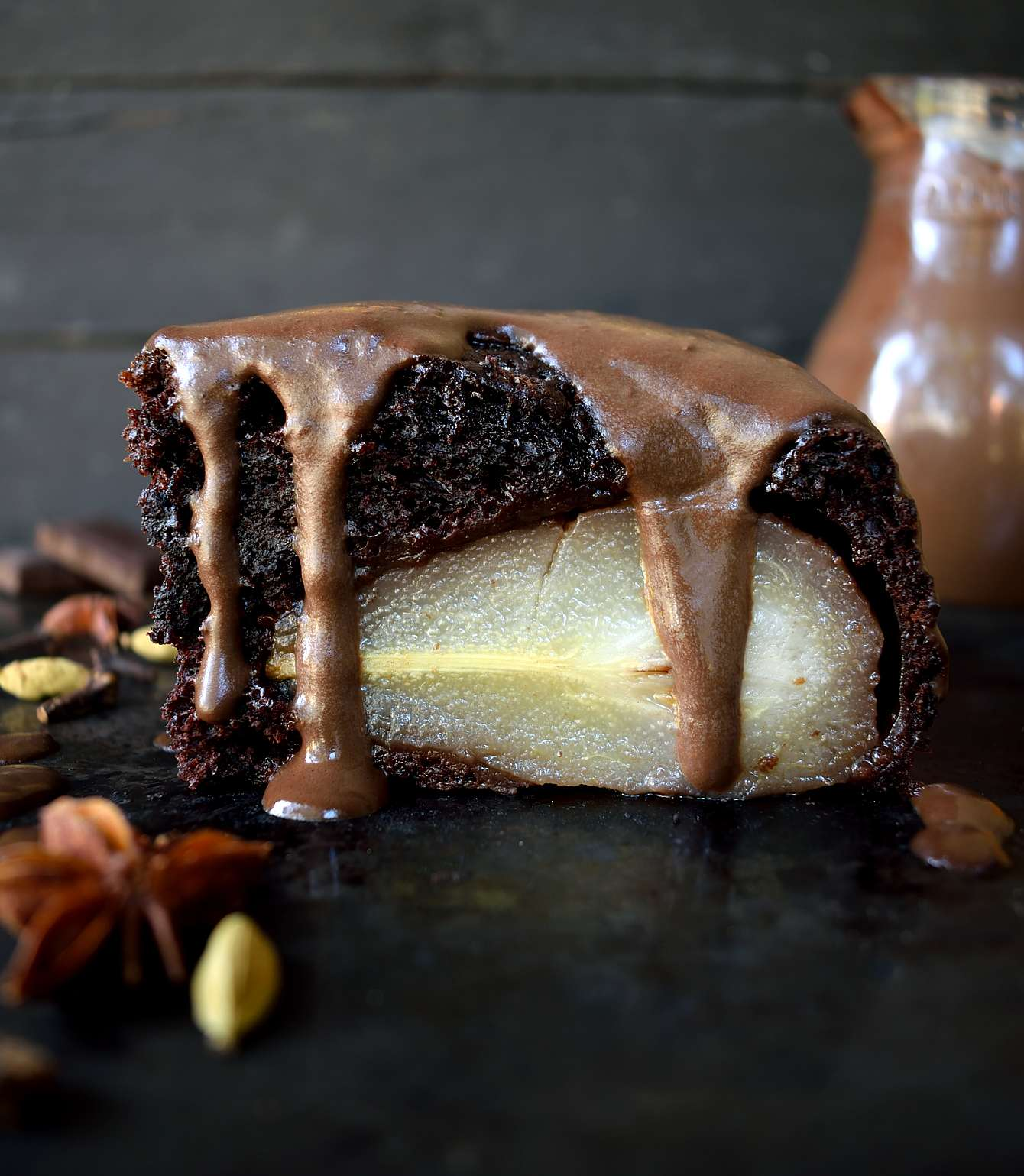 Vegan chocolate cake with poached pears is much easier than it looks. Pears poached in red wine and spices then baked into the middle of a moist chocolate cake and drizzled with chocolate sauce. An impressive and delicious vegan dessert.