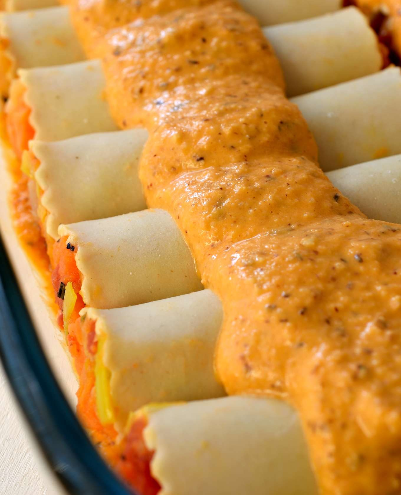 This vegan cannelloni recipe is a delicious soy-free dish to warm you up on a chilly evening. Roasted root vegetables are stuffed inside pasta tubes, smothered in a homemade romesco sauce and sprinkled with breadcrumbs for a crispy crust. This elegant dish uses the best of winter's seasonal vegetables and makes a great vegan holiday dish.