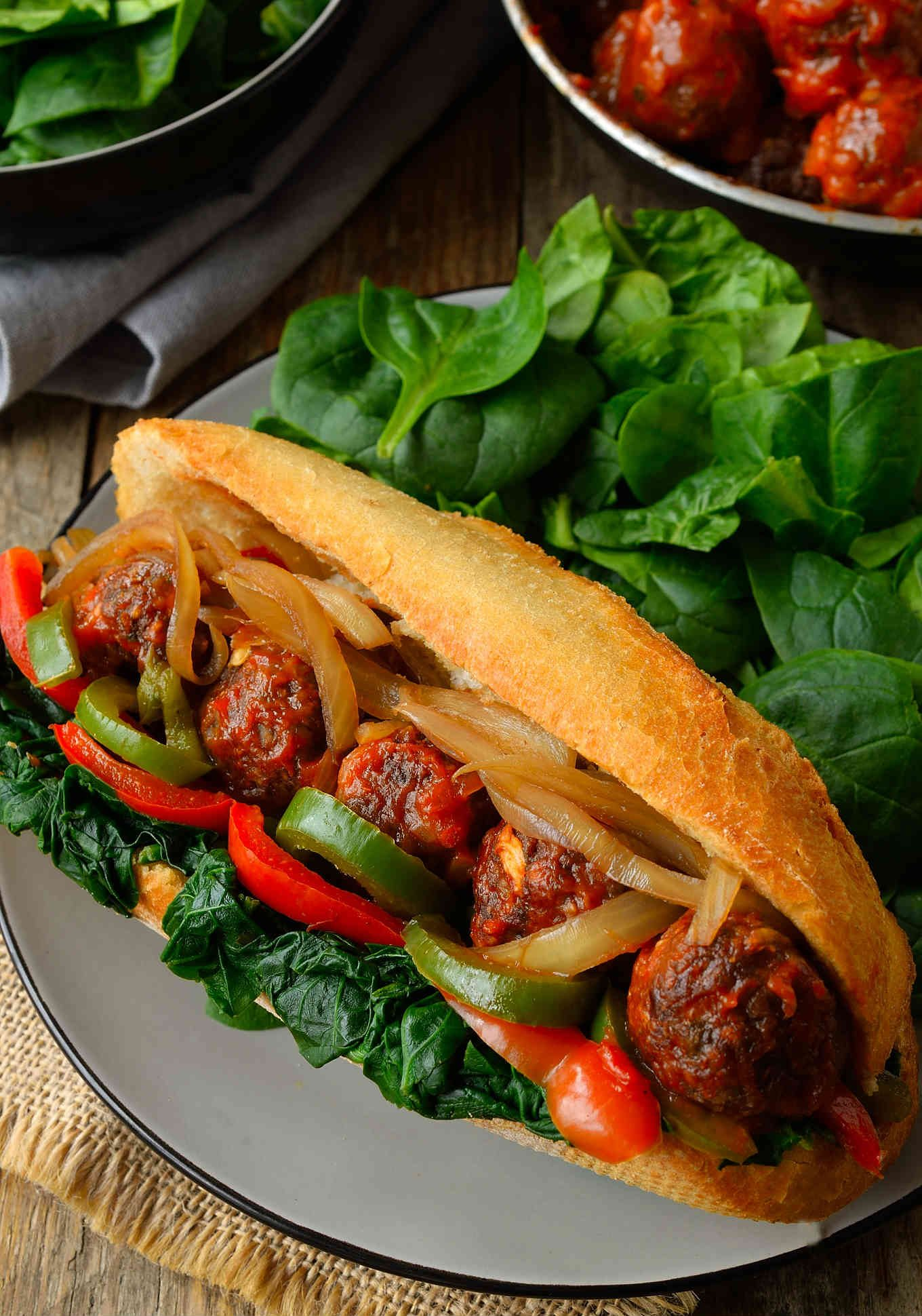 This vegan meatball sub sandwich is super hearty, super flavourful and chock full of veggies. Baked lentil and mushroom meatballs smothered in marinara sauce and served up in a crusty bun stuffed with spinach, onion and peppers. You might need a knife and fork to get these bad boys in your mouth!