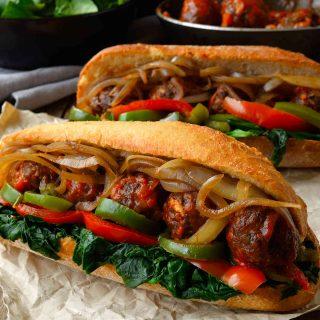Este sándwich de albóndigas veganas es realmente sustancioso, muy delicioso y lleno de verduras. Estas albóndigas de lentejas y champiñones con salsa marinara van servidas en bollos crujientes rellenos de espinacas, pimientos y cebolla. Es probable que necesites cuchillo y tenedor para comer este sándwich sub de albóndigas!