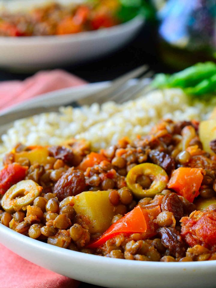 This vegan picadillo recipe is a delicious and colourful Cuban-style dish of spiced lentils, potatoes, tomatoes, olives and raisins. Served with rice, it's quick and easy to prepare for a weeknight dinner and the warming spices of cinnamon, cumin, cloves and nutmeg make it a comforting and hearty meal for chilly weather.