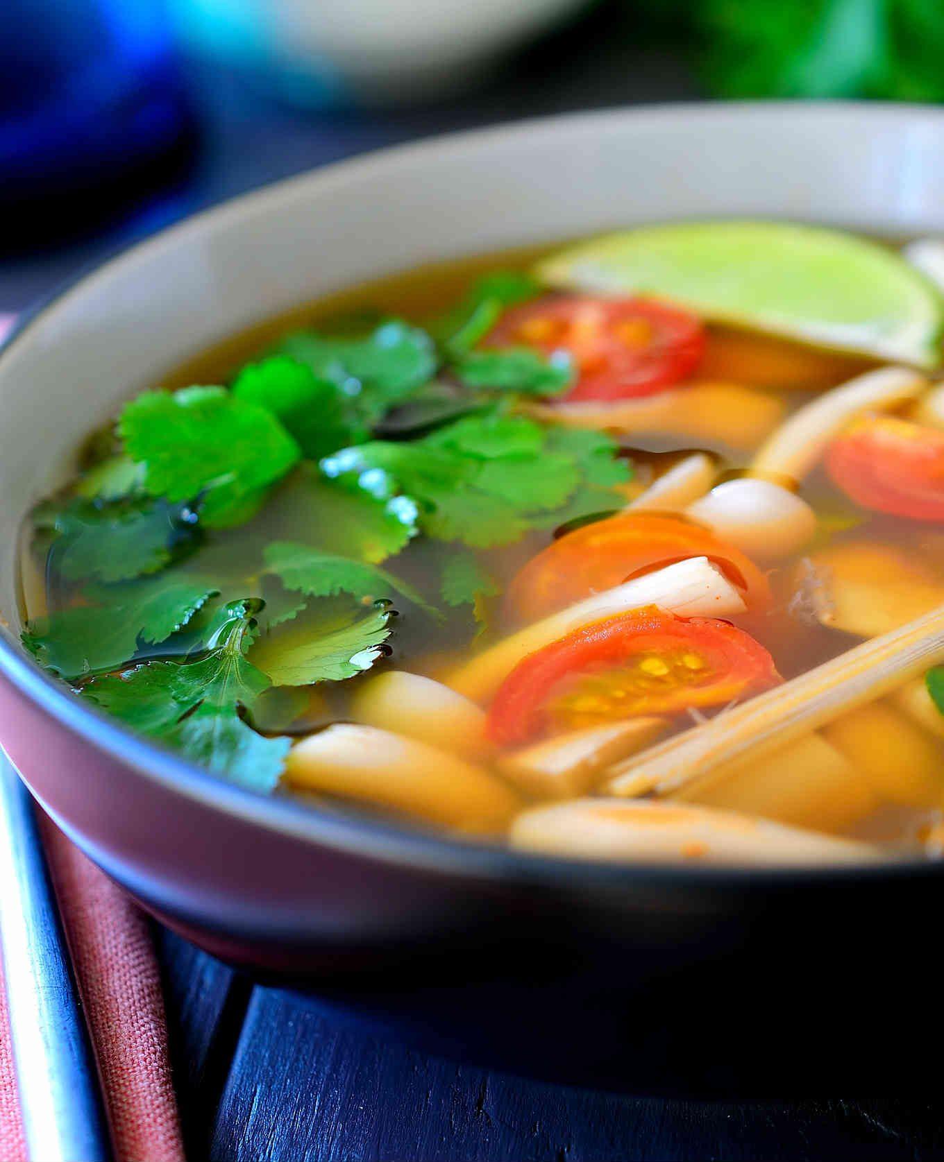 Esta receta de sopa tom yum es a la vez sabrosa, picante, ligera y vegana. Un caldo aromático y sabroso a base de setas asiáticas, citronella (limoncillo) y hojas de lima kaffir, aderezado con jugo de lima. Una cucharada de pasta de chili al final para un poco de picante, para entrar en calor, y ya tienes un bol de sopa caliente perfecto para una tarde fría de invierno.