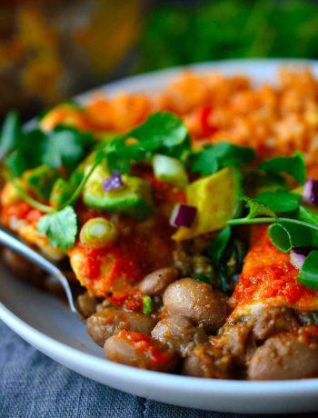 Esta receta de enchiladas veganas es muy sustanciosa, con su relleno de alubias pintas ahumadas y picantes cocidas lentamente con espinacas, una salsa para enchiladas casera rápida y fácil de hacer, y decoradas con cremoso aguacate, cebolla roja y cilantro fresco.
