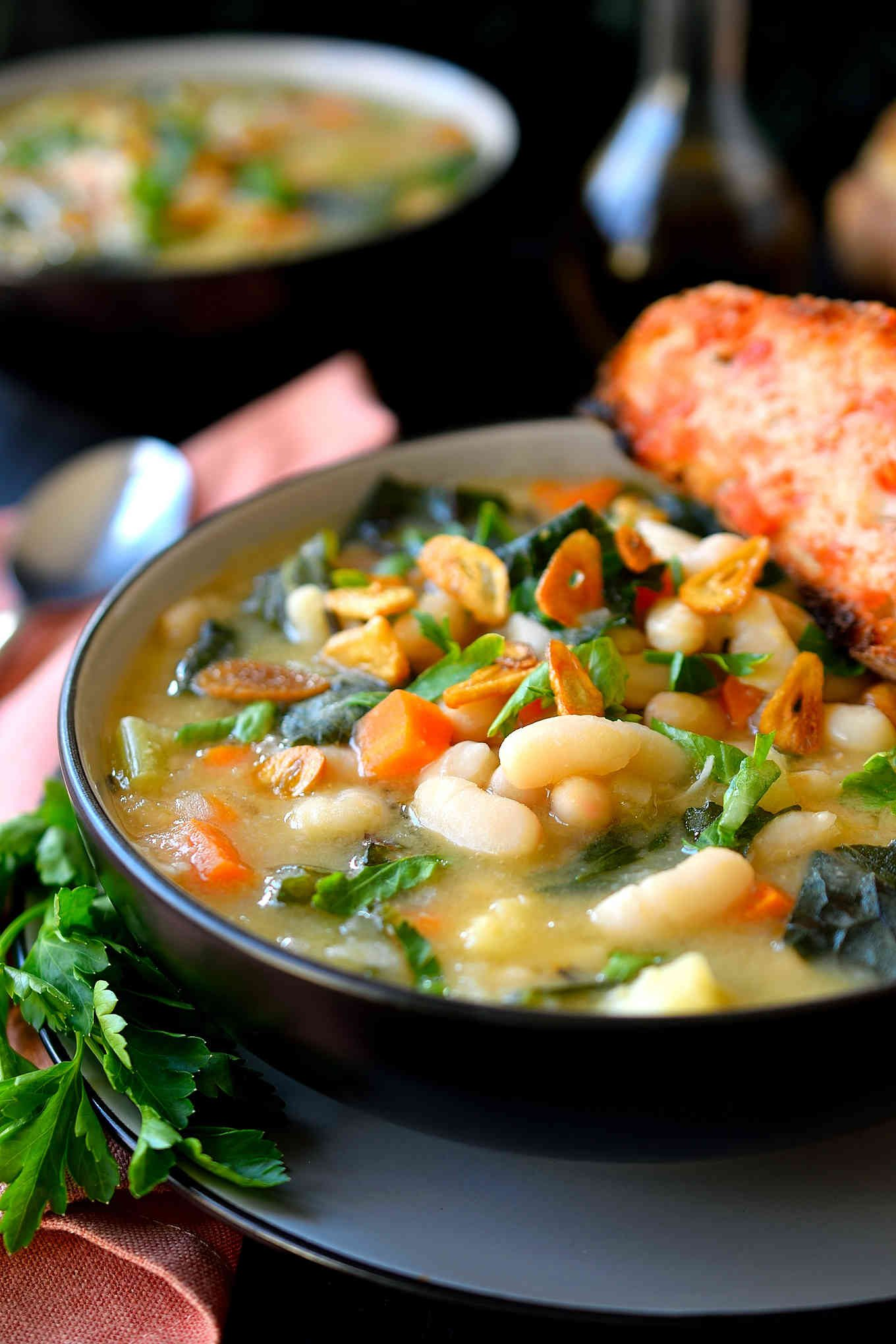 This vegan white bean and kale soup is easy to prepare in just 20 minutes, creamy and absolutely delicious! This is my version of the well-known Tuscan white bean soup with a secret ingredient in place of the parmesan to make it vegetarian- and vegan-friendly. This hearty soup is perfect for a busy weeknight dinner.