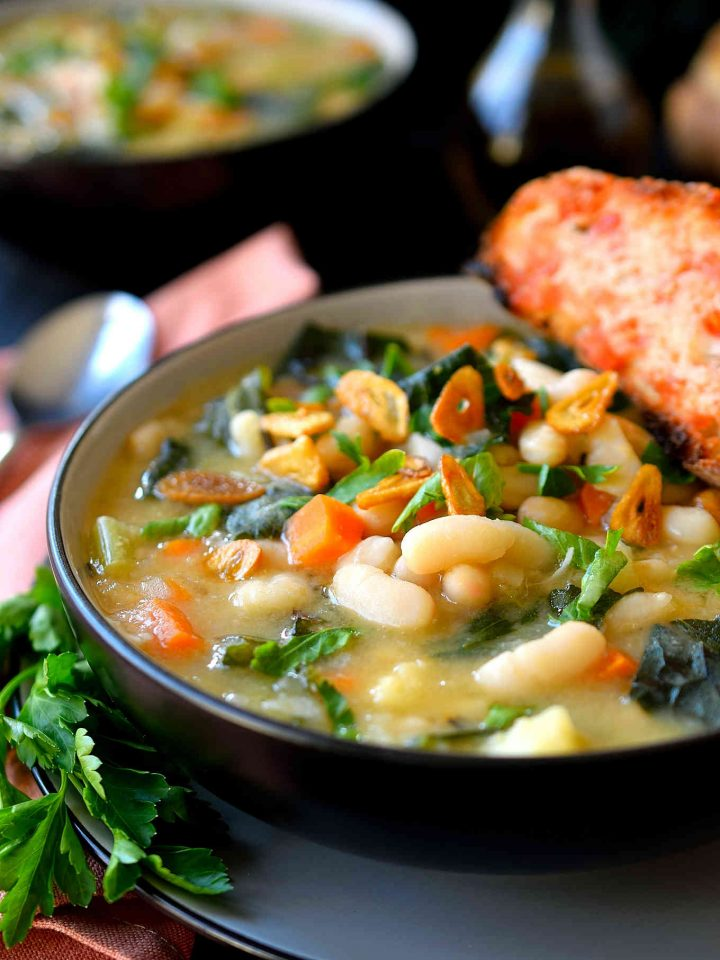 White bean and kale soup in a black bowl