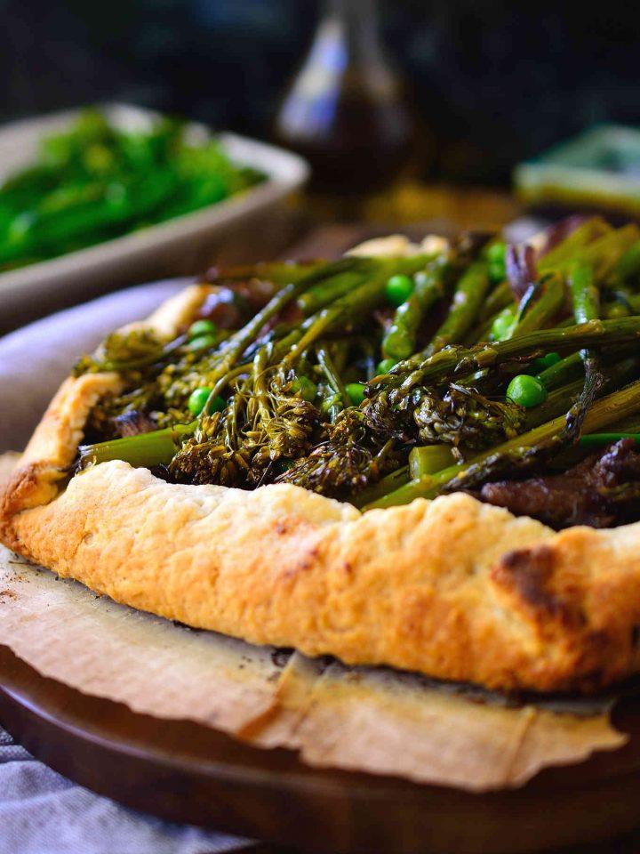 Esta galette de verduras lleva consigo todos los sabores de la primavera: espárragos trigueros, bimi (brócoli de tallo largo) y guisantes sobre una cama de col kale y queso ricotta vegano.
