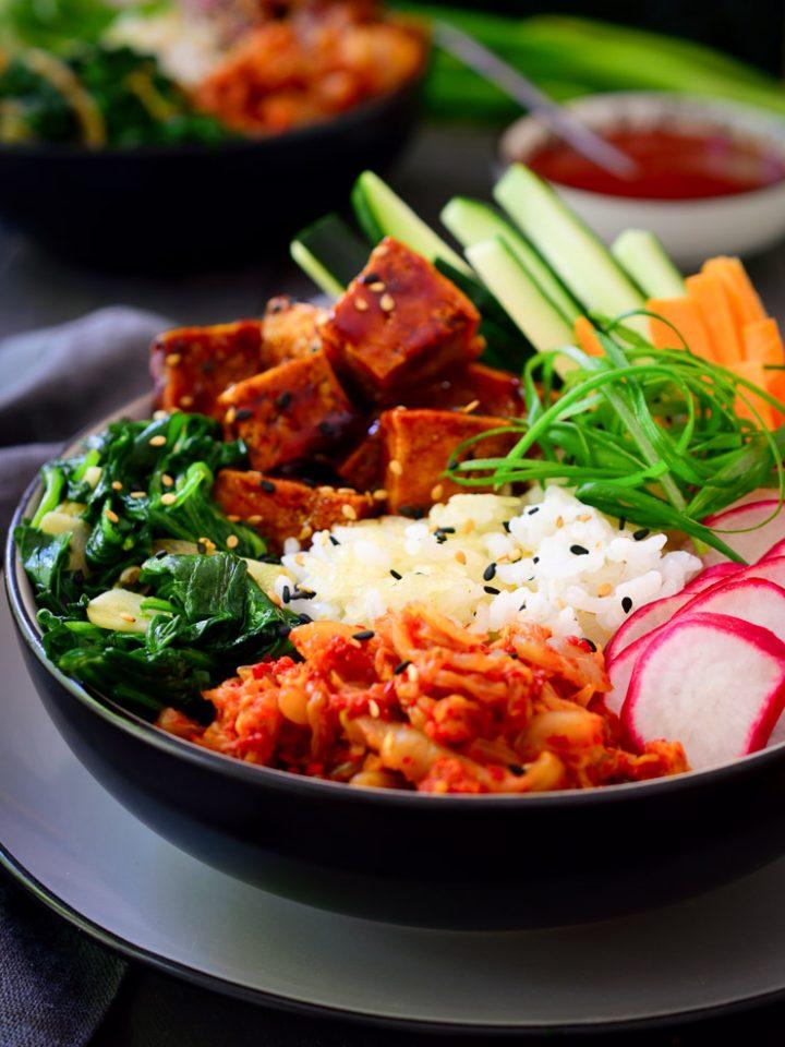 Esta receta de bibimbap coreano es fácil de preparar y está repleta de sabores y texturas. Empieza con una base de arroz frito combinada con un arco iris de verduras frescas y sofritas, y continua con lo mejor: tofu frito en una salsa de gochujang y kimchi fresco, sabor autentico de Corea!
