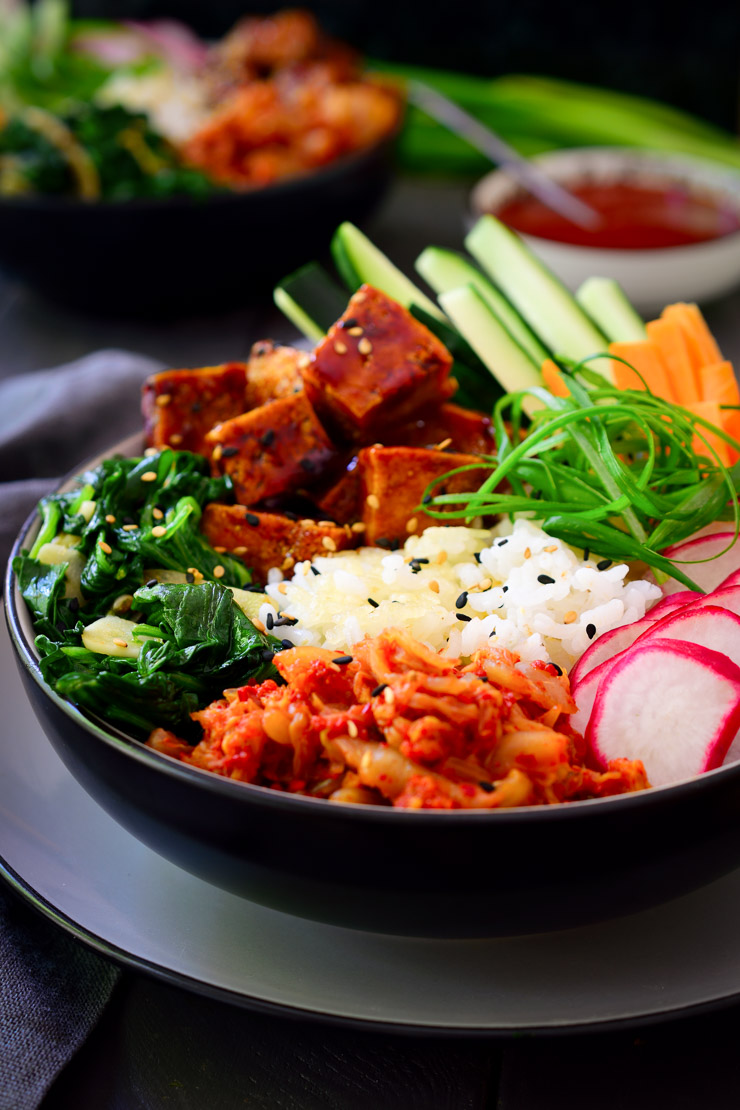 This recipe for vegan bibimbap is simple to put together and has a great combination of textures and flavours. It starts with a base of crispy pan-fried rice (no special equipment needed) and is topped with a rainbow of fresh and sautéed vegetables. Best of all is the crispy gochujang fried tofu and fresh kimchi on the side for a real taste of Korea!