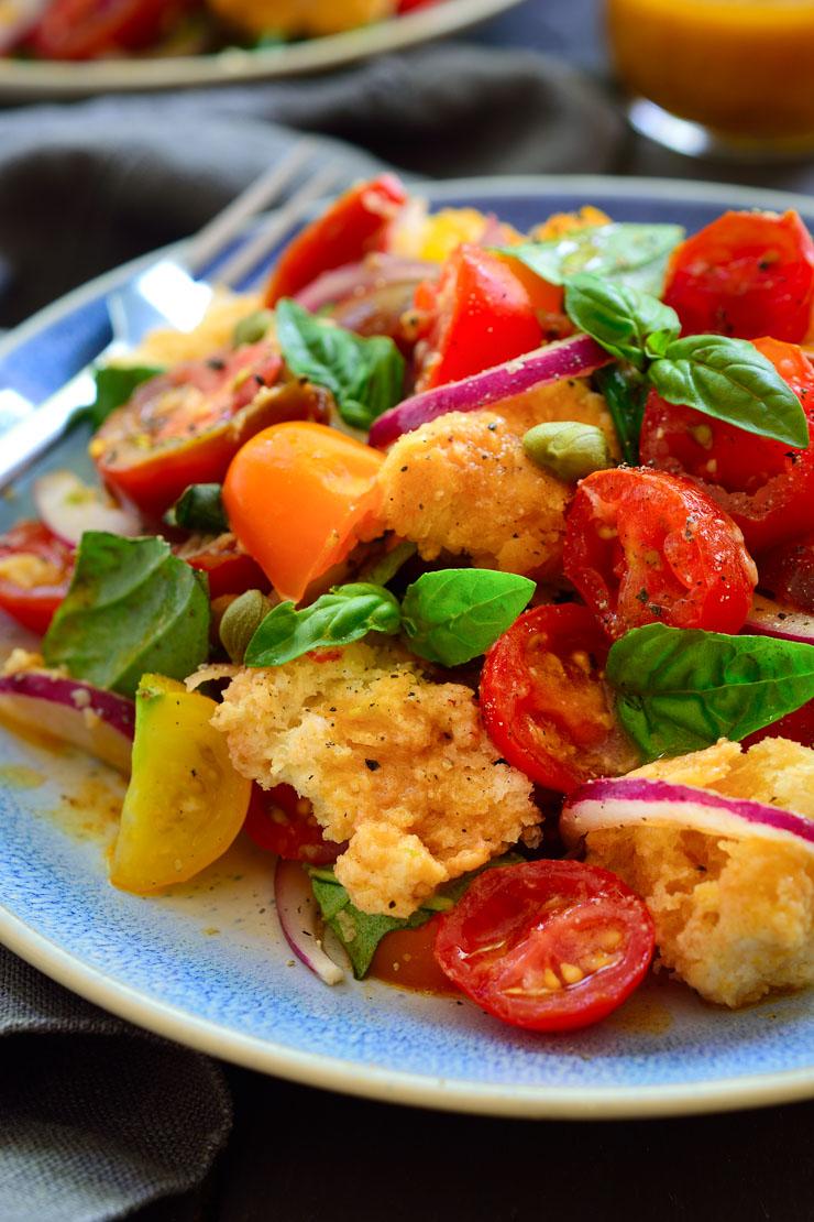 La panzanella es una ensalada italiana de tomate y pan; ingredientes humildes que irradian sabor. Tomates frescos, albahaca, cebolla roja, pan del día anterior y un aderezo ácido y umami (gracias a un ingrediente sorprendente) es todo lo que necesitas para disfrutar de esta ensalada colorida y deliciosa!