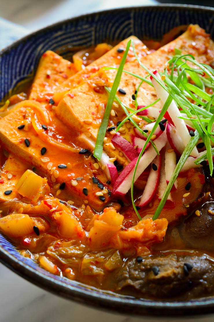 This vegan kimchi stew is quick and easy to prepare, packed with flavour and as spicy as you want it to be. Served with sliced tofu, shiitake mushrooms and rice on the side, it's a full and hearty meal that can be prepared in less than 30 minutes.