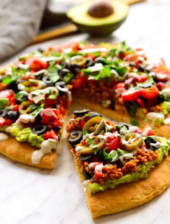 Esta pizza vegana representa el matrimonio entre dos de las mejores comidas en este mundo: pizza y nachos. ¿Cómo te quedas? Una masa de pizza cubierta de guacamole y decorada con carne vegana especiada, verduras, cilantro, jalapeños y un chorro de crema agria vegana.