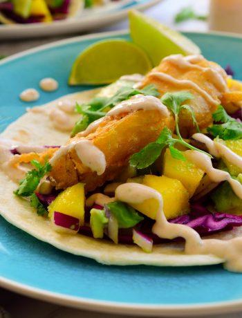 """Estos tacos de pescado veganos te cambiarán la vida. Crujiente """"pescado"""" vegano rebozado servido encima de col lombarda aderezada con lima y sal, y una ensalada refrescante de mango y aguacate. Todo decorado con un chorro de una salsa cremosa de chipotle y lima."""