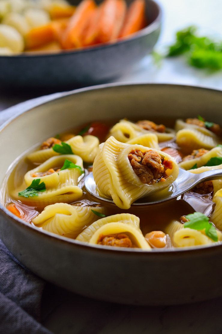 A bowl of vegetarian pasta soup with seitan meatballs stuffed inside the pasta shells.