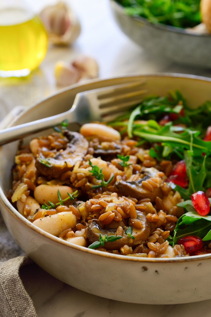 Mushroom farro with beans in a bowl with a rocket and pomegranate salad on the side.