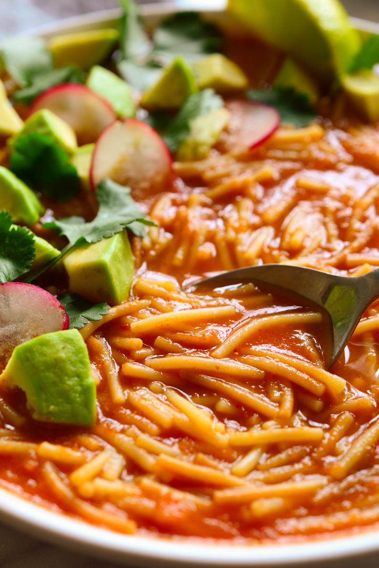 Sopa de fideo served in a bowl with a spoon.