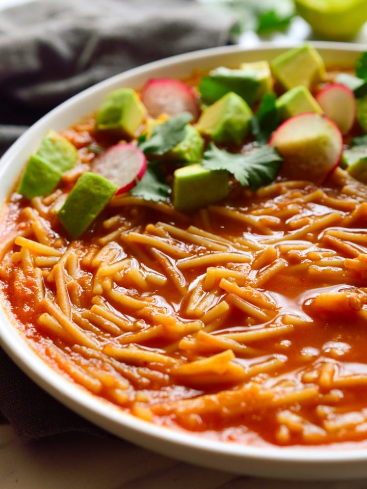 Sopa de fideo, Mexican noodle soup, in a bowl garnished with avocado, cilantro and radish.