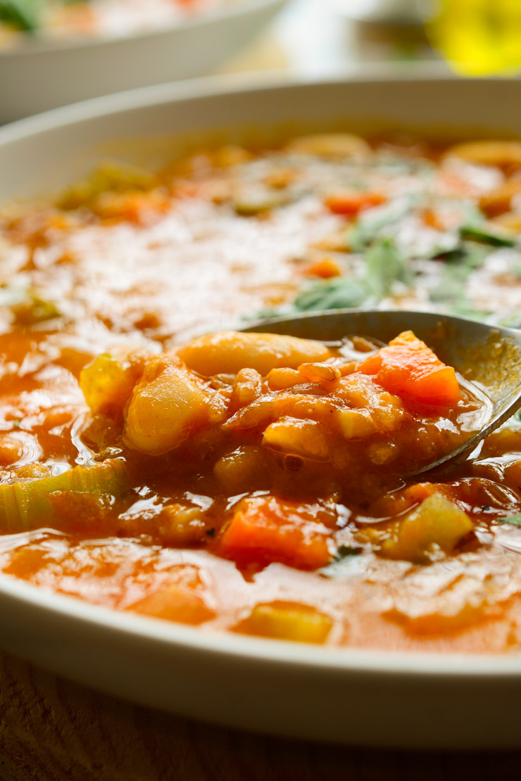 A closeup photo of vegetable farro soup with a spoon in the bowl.