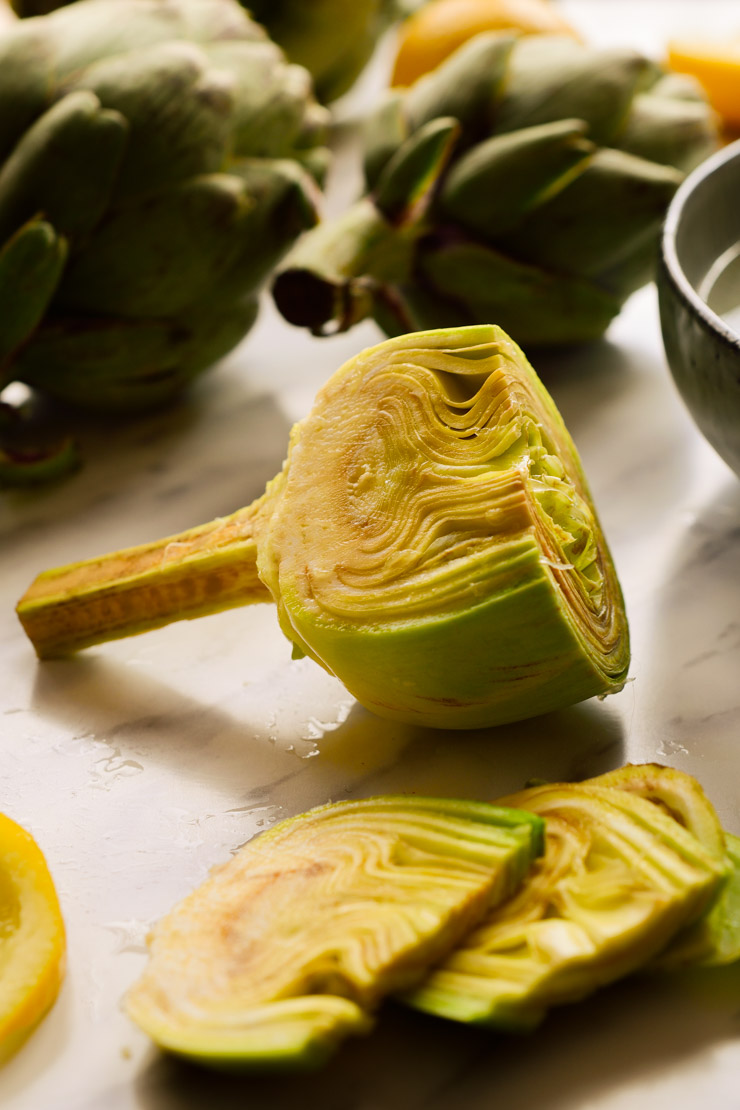 A peeled fresh artichoke with three thin slices cut from it.