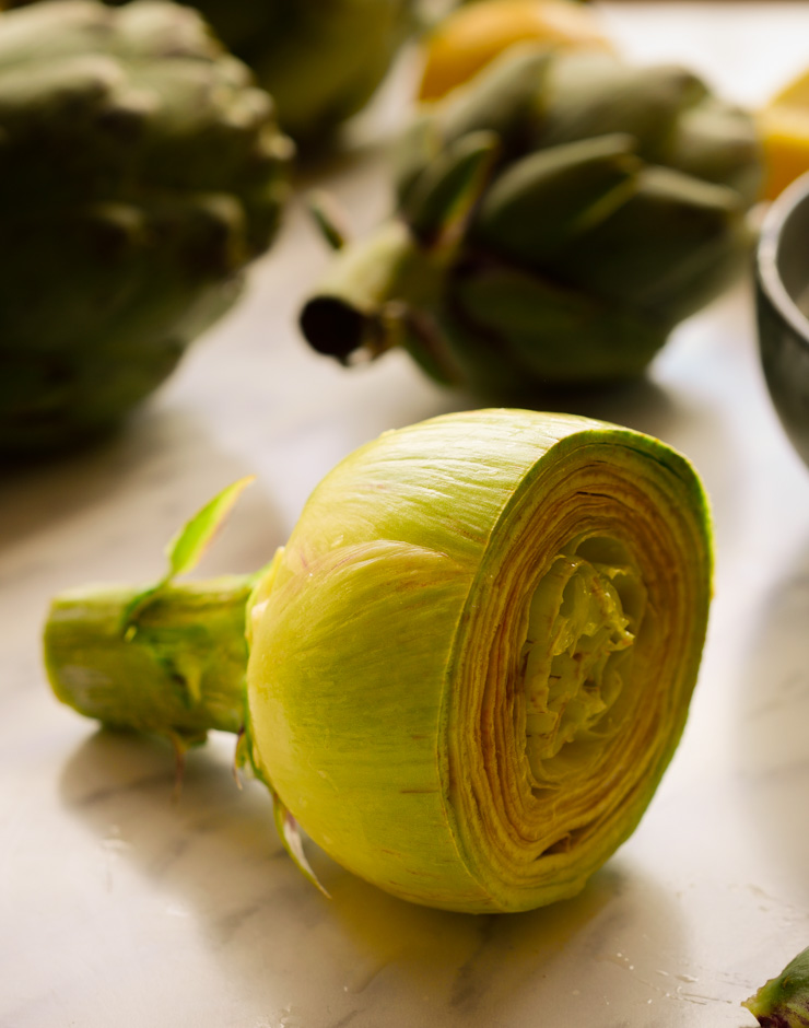A fresh artichoke with the dark green leaves peeled off.