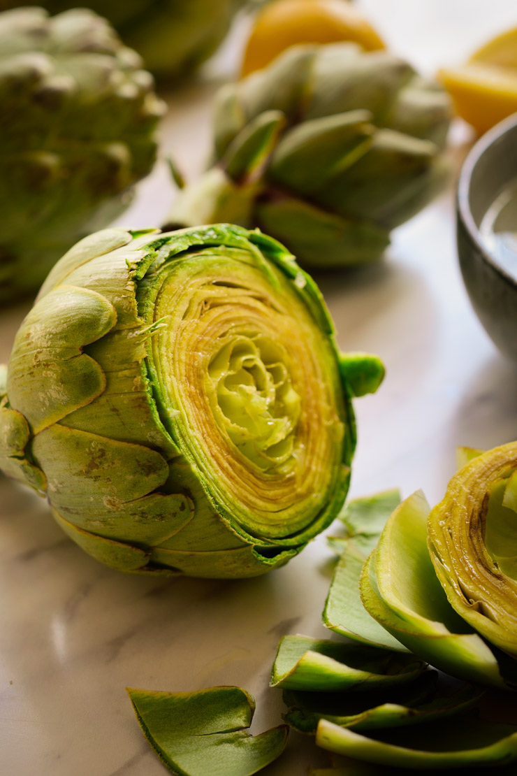A fresh artichoke with the top third cut off.