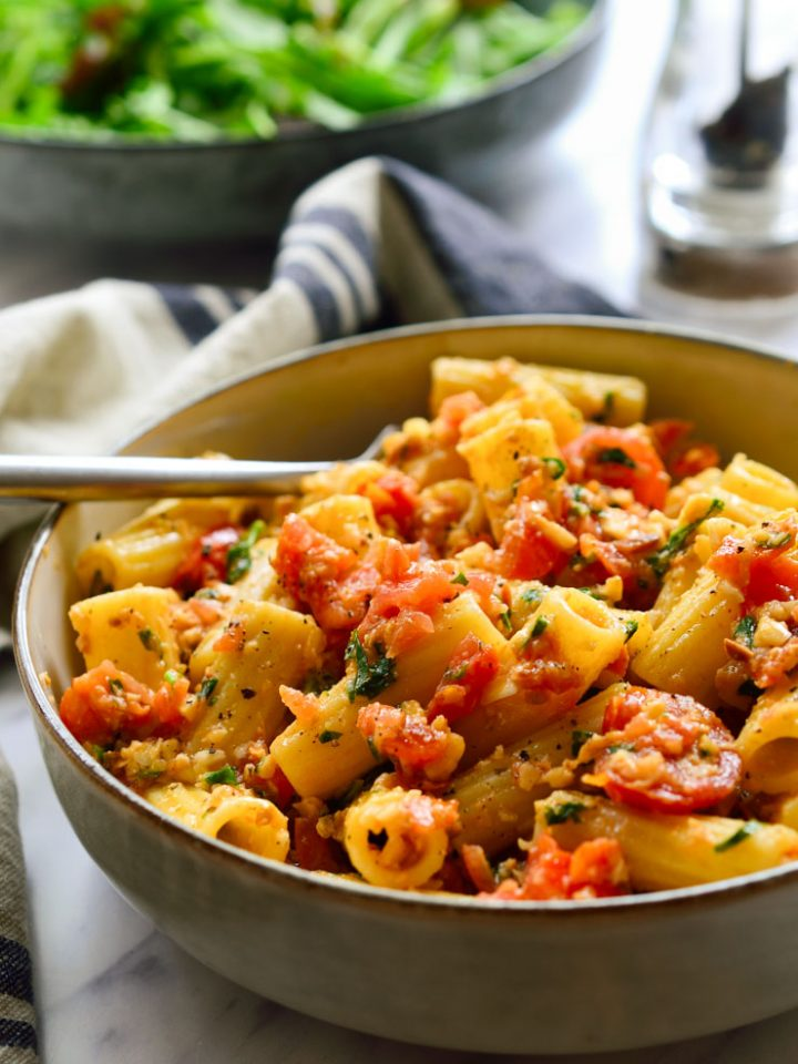 Almond tomato pesto pasta in a bowl.