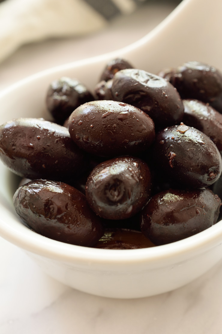 Black olive in a white bowl.