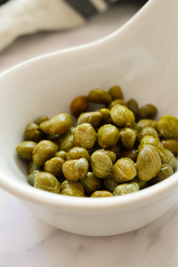 Capers in a white bowl.