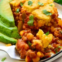Vegan tamale pie on a plate served with avocado slices and fresh cilantro.