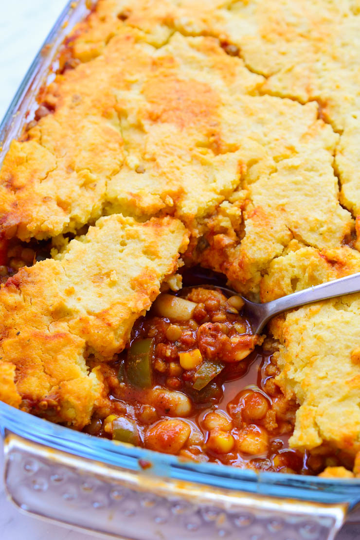 Vegan tamale pie in a pan with a slice taken out.