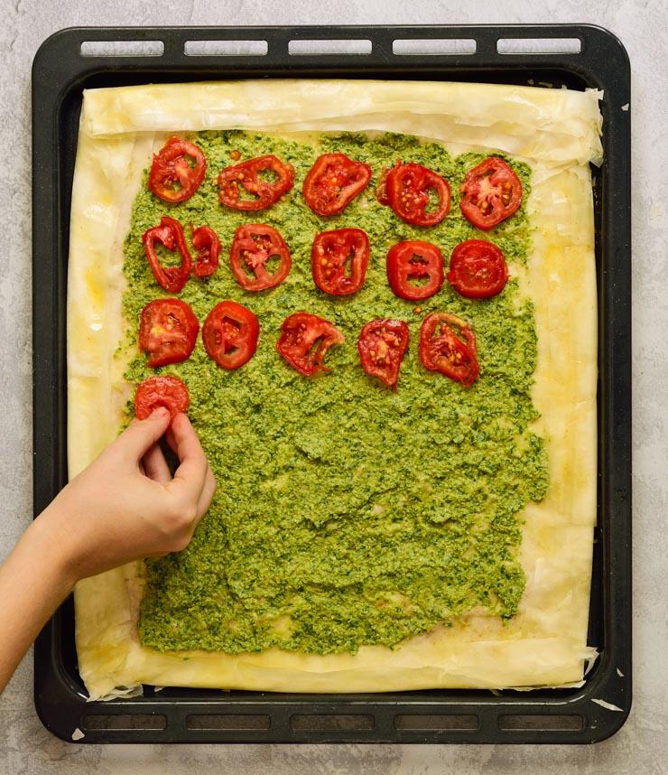 Colocando los tomates en la tarta.