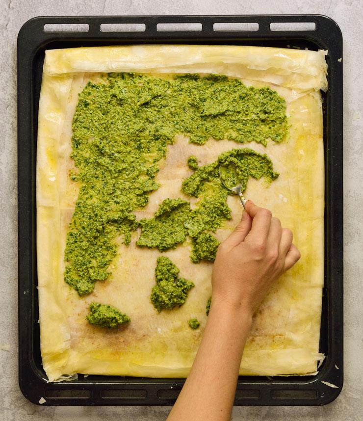 Untando el pesto en la tarta.