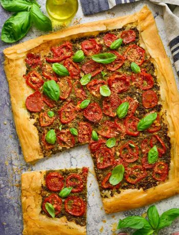 Vegan tomato pesto tart with a slice cut out of it.