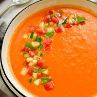 Watermelon gazpacho garnished with cucumber and diced watermelon in a white bowl