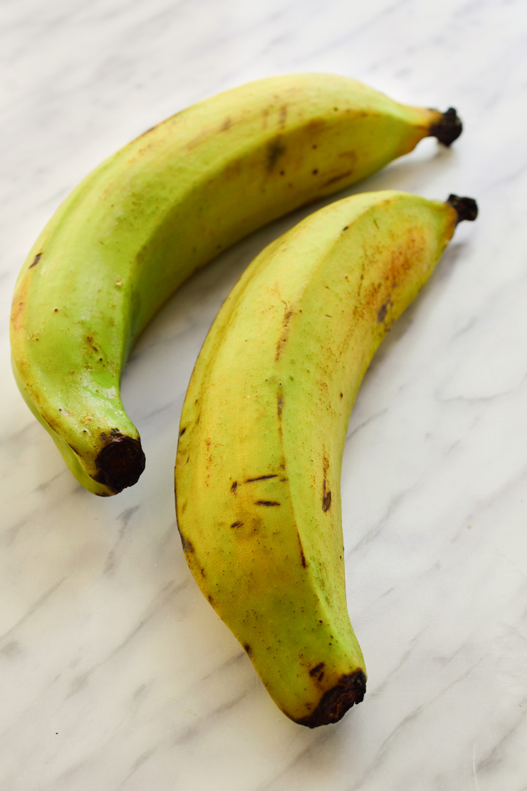 Two green plantains unpeeled.