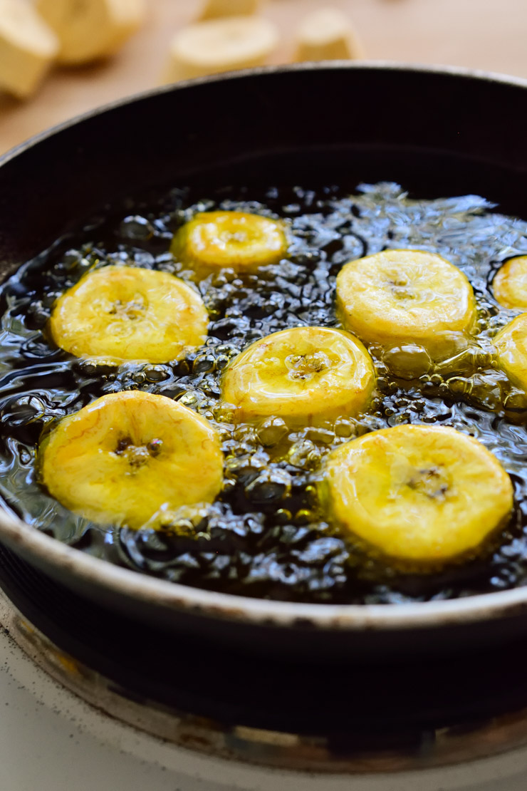 Green plantains slices in a frying pan.
