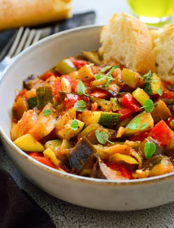 Pisto vegetable stew in a bowl with bread on the side.