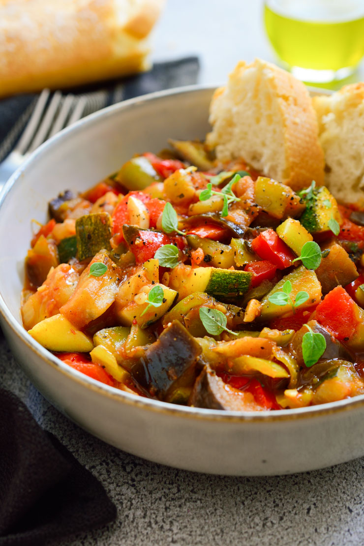 Pisto vegetarian stew in a bowl with bread on the side.