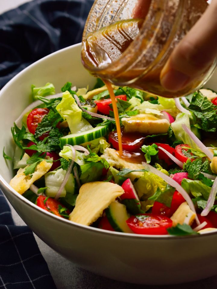 Lebanese salad mixed in a bowl with dressing being poured over.