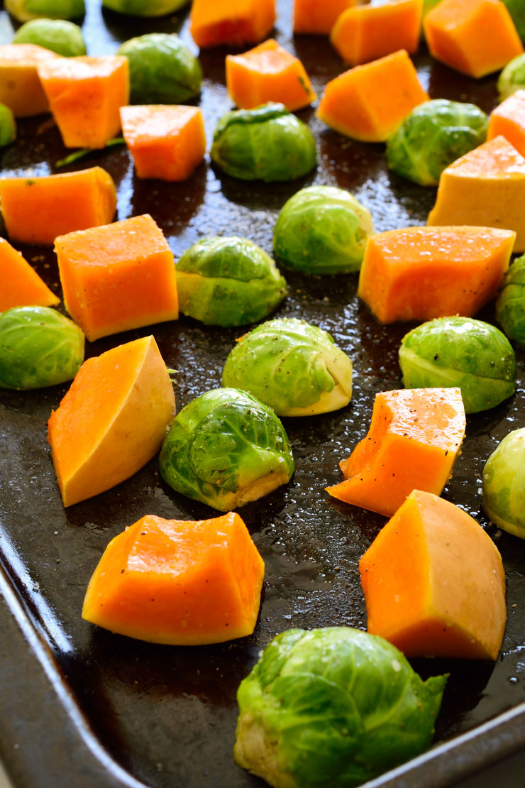 Butternut squash and Brussels sprouts on a pan ready to roast.