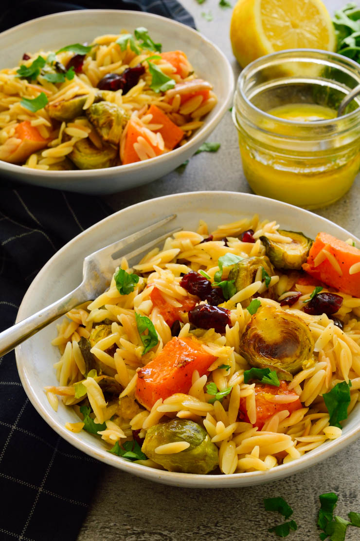 Roasted winter vegetable orzo pasta salad in a bowl with a fork.