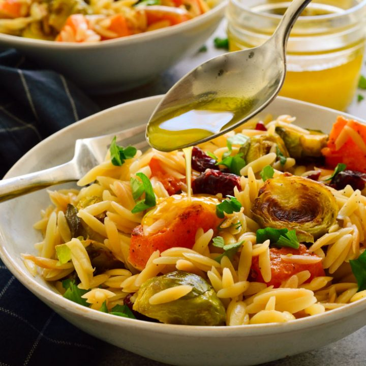Roasted winter vegetable orzo salad in a bowl with lemon vinaigrette drizzled over.