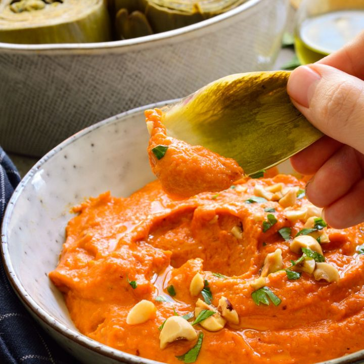 Romesco sauce in a bowl with an artichoke leaf being dipped in.