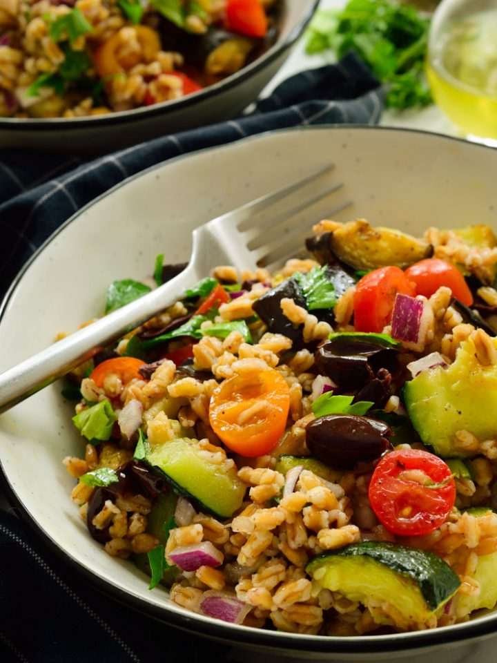 Mediterranean farro salad in a white bowl with a fork.